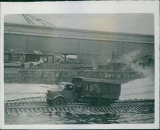 """Loaded lorry moving along the """"Swiss roll"""" while large waves (trough to crest 4 ft) are produced by an M.T.B. racing alongside. 1945."""