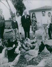 Georges Bidault and other people looking at hens.