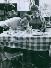 A man and a woman on a dining table.