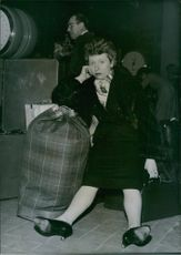 French singer and actress Patachou have sat with a bag by spreading her two leg and looking towards the camera