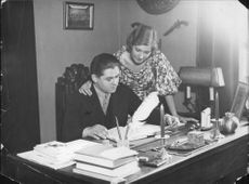 "Johan Jonatan ""Jussi"" Björling reading some documents with his wife."