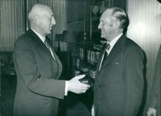 William H. Rogers and Sicco Leendert Mansholt smiling and facing each other.