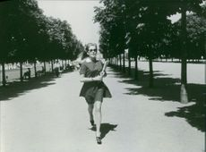A woman walking on road.