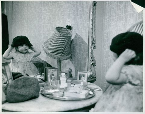 A kid fitting a cap in front of the mirror.