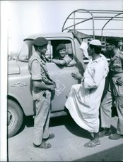 Soldiers having conversation with a man in street and smiling.