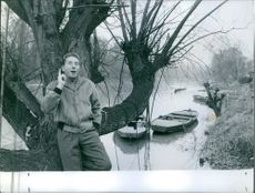Charles Trenet leaning on a tree beside a river.