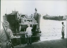 An American amphibious armored vehicle starts down the lowered ramp of an LCT vessel to the beach  at Cape Gloucester, new Britain Island, during landing operations there by U.S. Marines.
