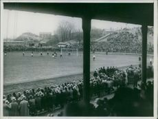A Football match while the crowd watching.