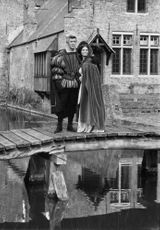 Jean-Claude Pascal and a woman standing on wooden bridge.