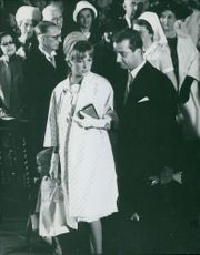 Albert II of Belgium and his wife Queen Paola of Belgium in church with other people.