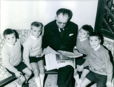 A man reading a newspaper with his four children. 1967.