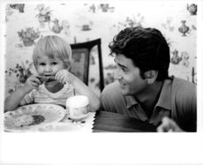 Michael Landon watching a kid as he eats.