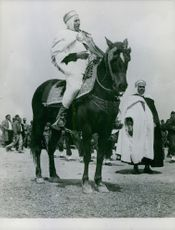 Man sitting on the horse, people around him.