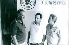 Three men, who are members of an association, having a conversation, 1970.