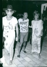 Michele Mercier photographed with two men, one wearing face mask.