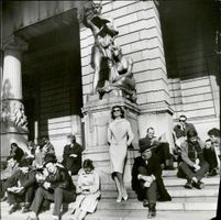 People sitting on the steps by a monument.