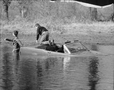 Roger Vadim sitting on car which downing in water.