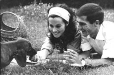 A woman and a man lying on a grassy ground with a dog.