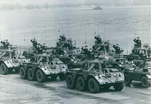 Soldiers standing with their tanks and artillery and saluting.