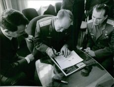 A photo of army officers and generals siting together and writing something on paper. 1965