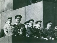 A photo of leaders standing looking something far.