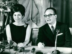 A prominent man with a woman in a press conference.