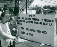 """A mother carrying her child read the message on board """"Good luck on your passage to freedom"""" before boarding the ship in Vietnam."""