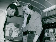 Woman listening to radio, a man standing beside looking at her.