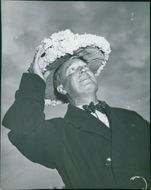 Maurice Chevalier looking up.