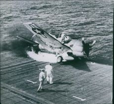 A rescuer tries to rescue a burning fighter plane on an aircraft carrier.