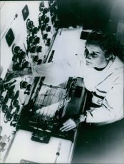 A photo of a woman standing and controlling in the control room.