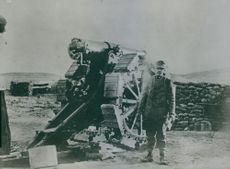 Italian Soldier standing beside cannon. 1915