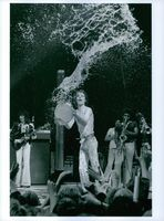Man throwing water at audience while performing during an event.