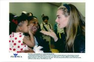 Actress Brooke Shields gives kisses to 15-month-old Sabrina Friends with her mother Brenda at the opening of Andre Agassis Boys and Girls Club