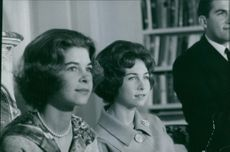 Royal women siting and looking away.
