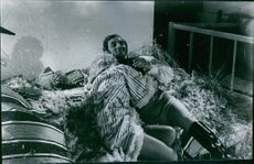 France Anglade lying on dried grass with a man and smiling.