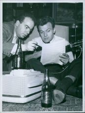 Actor Georges Ulmer is reading, while a men is showing something on the page
