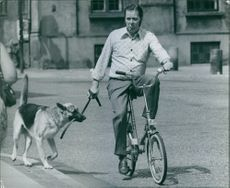 Man cycling a dog walking beside.