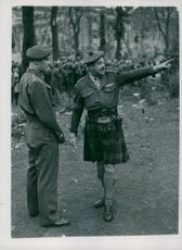 A recent picture of Lt. Col. T.C. Irvine, M.C. (in kilt) taken during the raids on black marketeers, gives instructions to one of his soldiers.