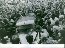 People gathered around a car, man getting off from the car and policemen guarding.