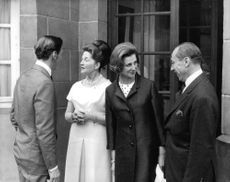 Princess Alexandra talking to a man, smiling, with Angus Ogilvy talking to a woman, 1965.
