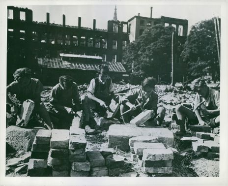 Mortar adhering to the larger bricks is chipped off by a group of boys in the yard of the Kepler Mittelschule. The average age of these boys is 13 years. In the background is the bomb-wrecked school building.