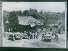 A jeep driver stops for a break at some natives during an inspection trip through the Japanese conquered areas.