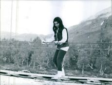 Maude Adelson crossing the hanging bridge over the river.  - 1964