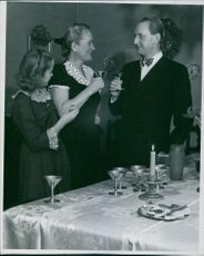 Einar Beyron and Brita Hertzberg standing together and having drinks with their daughter.