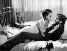 Carroll Baker lying on bed with man.