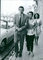 Robert Hossein walking with his wife.