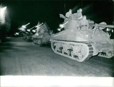 Military men in tanks moving on the road.