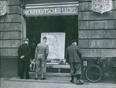 Men on the sidewalk looks at a display on the building during the war in Berlin,1940.