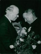 Man giving flower to Maurice Chevalier.